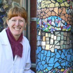 katrina frazer stands beside mosaic school artwork