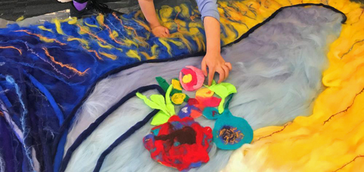 large felt artwork in progress student hands placing felt flowers