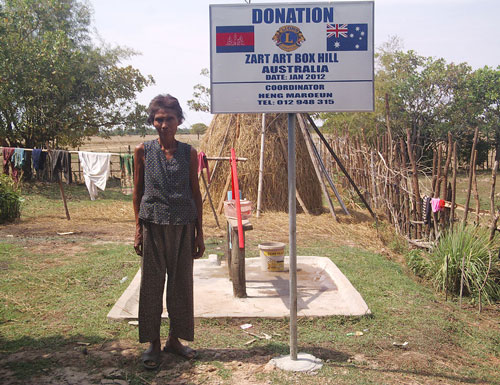 Cambodian adult female standing in front of one of the wells that were donated to Indonesia, with the Zart Art donation pole in the foreground